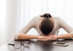 woman-with-eyeglasses-and-head-on-table
